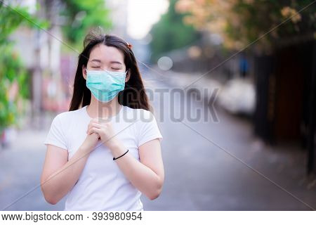 Selective Focus. Asian Woman Wearing A Green Medical Face Mask Stands To Pray In Order To Survive Th