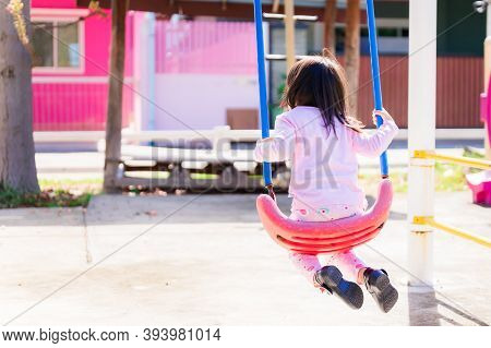 Back Side Young Asian Girl In Morning Playing Swing On Playground After Waking Up. She Bent Her Legs