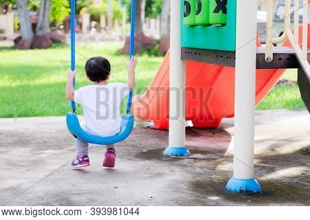 Back Side View Of Asian Toddler Boy Is Sitting On A Swing Gently. Peace Of Mind On A Winter Afternoo