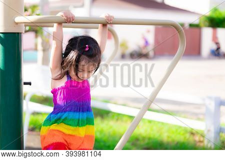 Cute Asian Little Kid Girl Are Wearing Colorful Clothes Hanging On The Bars With Both Hands. Child L