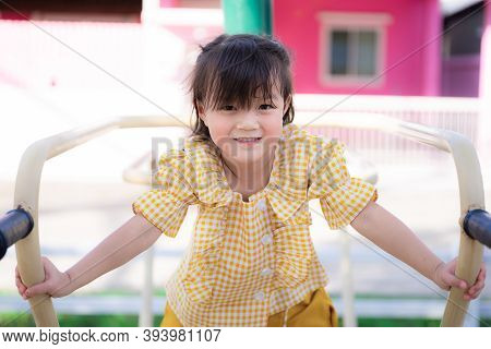 Active Asian Child Girl Is Climbing Playing And Exercising. Adorable Girl Is Wearing A Yellow-white