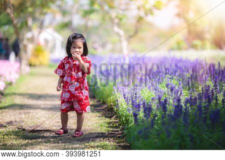 Happy Asian Child Girl Wearing Red Japanese Dress Stands, Opens Her Mouth And Smiles. Children Take