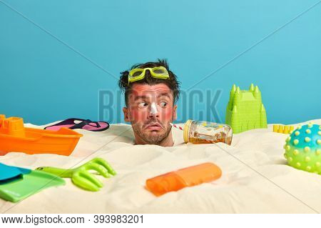 Outdoor Shot Of Surprised Male Face Stuck In Sand, Gets Sunburned At Beach, Applies Sunblock On Nose