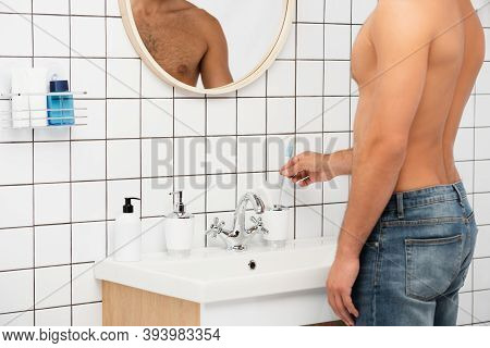 Cropped View Of Man Taking Toothbrush From Toiletries In Bathroom
