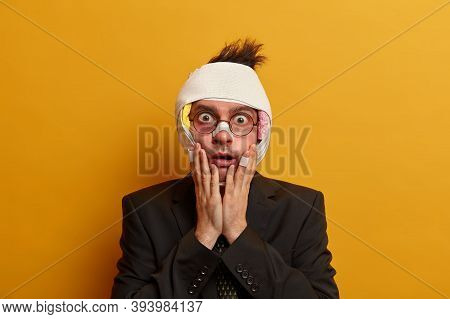 Stunned Shocked Man Looks At Himself In Mirror, Has Various Bruises And Abrasions On Face After Acci