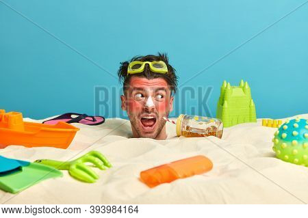 Emotive Young Man Cries Loudly, Looks Aside With Annoyed Expression, Wears Goggles, Got Sunburn On F