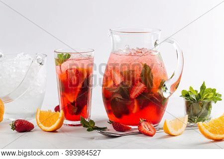 Side View On Glass And Jug Of Fresh And Cool Red Strawberry Lemonade With Mint And Orange