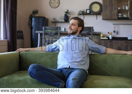 Handsome Young Business Man Is Looking Relaxed While Sitting On The Couch At Home.