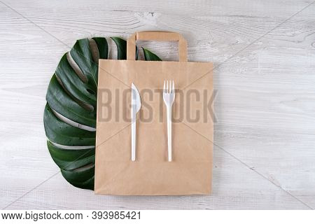 Plastic Fork, Knife On Paper Bag. Eco-friendly Food Packaging And Cotton Eco Bags On Gray Background
