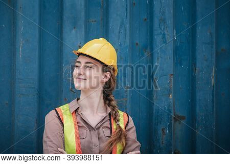 Portrait Of Confident Transport Engineer Woman In Safety Equipment Standing In Container Ship Yard.