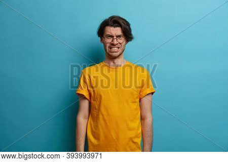 Irritated European Hipster Clenches Teeth With Annoyance, Looks At Camera With Mad Face, Wears Casua