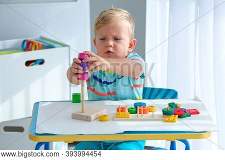 Little Boy 2 Years Old Is Played With A Wooden Pyramid. Educational Logic Toys For Children. Montess