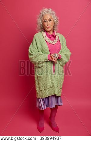 Full Length Shot Of Fashionable Mature Lady Dressed In Stylish Jumper, Pleated Skirt And Shoes, Pout