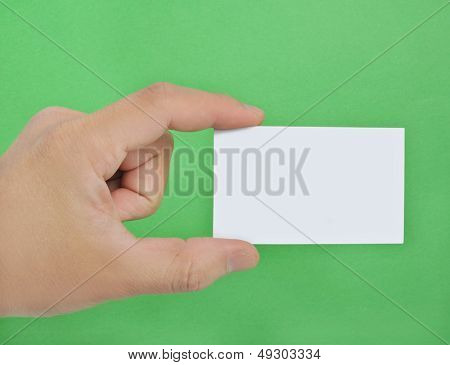 Blank business card in hand on  green background