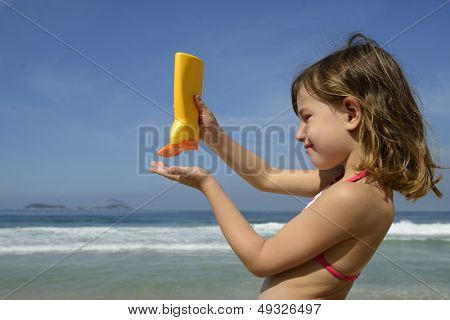 Child applying sunscreen lotion on the beach