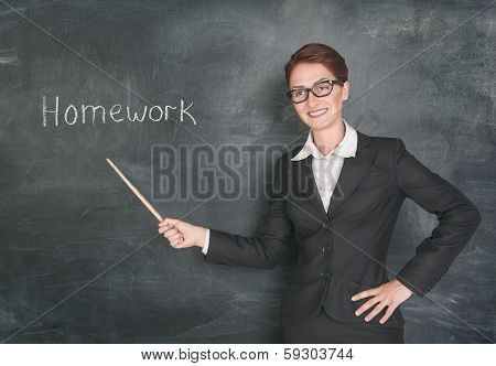 Smiling teacher with pointer and phrase Homework on blackboard chalkboard poster