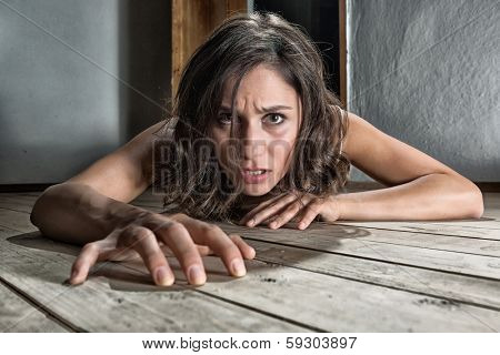Scared woman crawling on the floor of a derelict house