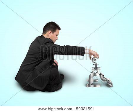 Businessman Sitting And Stacking Sliver 3D Symbols