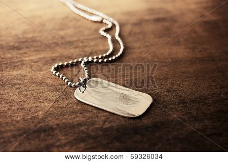 Blank silver tag on a ball chain, on a old wooden desk.