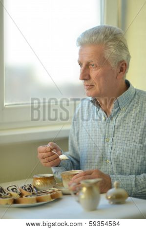 Elderly man with cup of tea