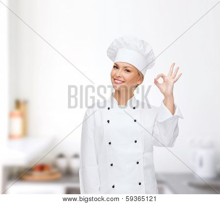 cooking, gesture and food concept - smiling female chef showing ok hand sign