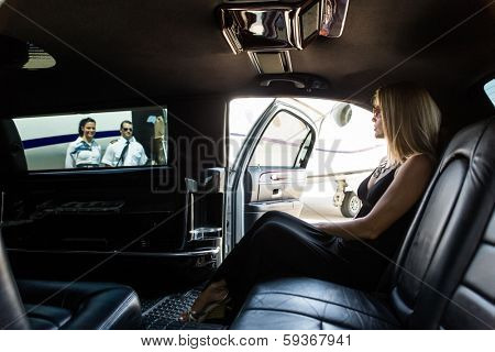 Elegant woman in limousine with airhostess and pilot near private jet at terminal