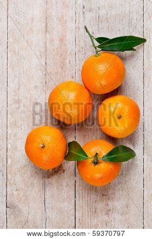 five tangerines with leaves on a wooden background