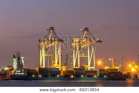 Container Cargo Freight Ship With Working Crane Bridge In Shipyard At Twilight.