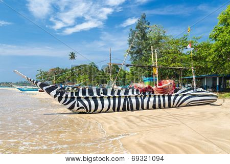 WELIGAMA, SRI LANKA - MARCH 7, 2014: Traditional Sri Lankan fishing boat decorated with zebra style stripes on sandy beach. Tourism and fishing are two main business in this town.