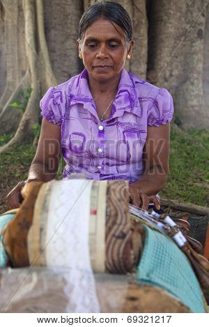 WELIGAMA, SRI LANKA - MARCH 7, 2014: Local woman making handmade lace decorations. Traditional handmade culture is still strong in these small villages.