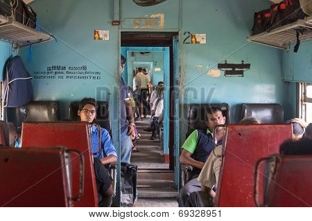 HIKKADUWA, SRI LANKA - MARCH 12, 2014: Commuters sitting in train to Colombo. Trains are very cheap and poorly maintained but it's the best option to witness a bit of everyday local life.