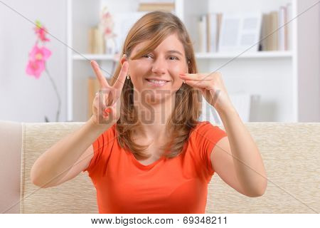 Beautiful smiling deaf woman using sign language showing V and E letters as a part of love word