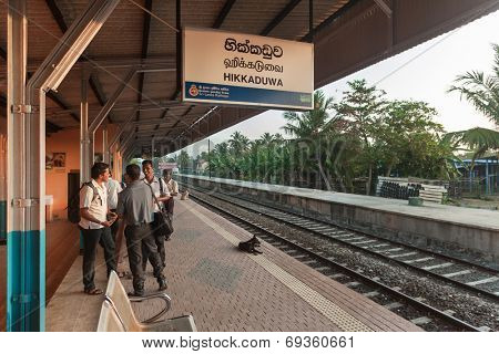 HIKKADUWA, SRI LANKA - FEBRUARY 22, 2014: Commuters wait for train at Hikkaduwa station. Trains are very cheap and poorly maintained but it's the best option to witness a bit of everyday local life.