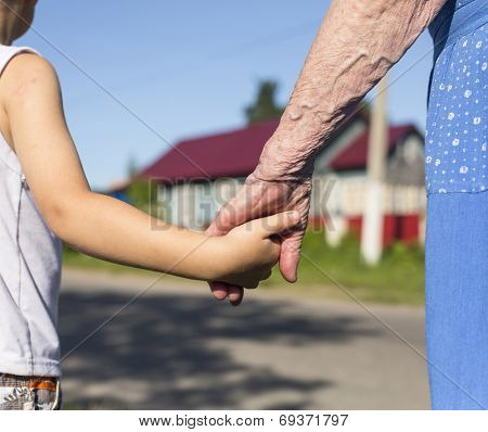 Hands of grandmother and child.