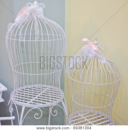 Two bird cages with white metal as a symbol of captivity and being trapped or in a confined prison