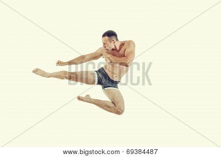 One Caucasian Man Exercising Boxing Jumping In The Air Kicking