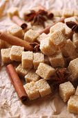 Brown sugar cubes and spices on paper background poster