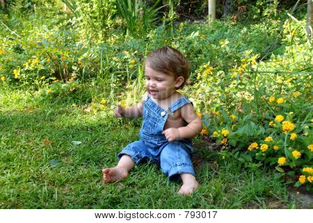 Boy Playing Outside in Blue Overalls