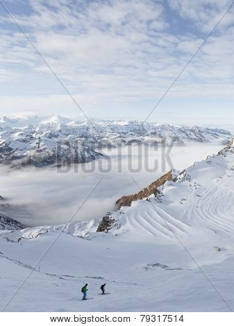 Skiers Descend A Steep Hill