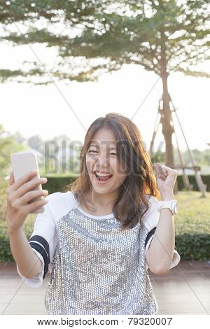 Portrait Of Young Woman Watching To Mobile Phone Screen With Surprising And Happiness Face