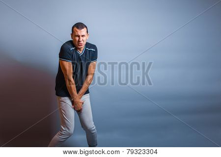European the man holding his hands over groin in pain on a gray
