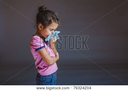 girl blowing his nose into a handkerchief