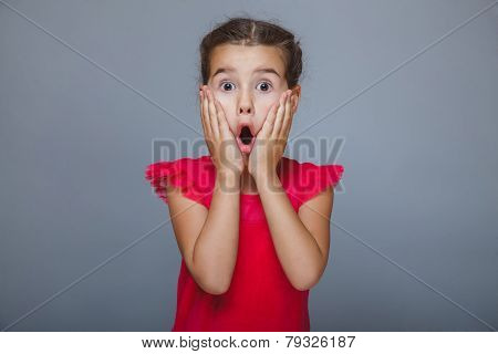 Girl child in red dress suffers surprise on gray background