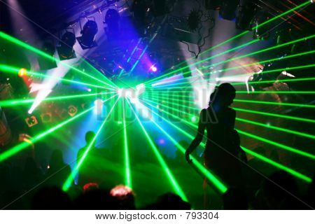 Silhouette of dancing woman between green laser light