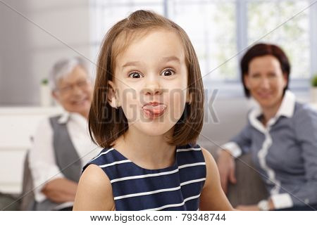 Cute little girl sticking tongue, making funny face, granny and mother looking from background.