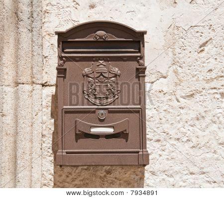 Brown Post box on wall.