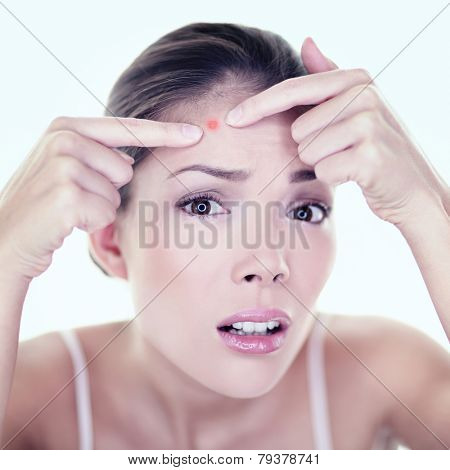 Acne pimple skin blemish spot skin care girl. Beauty care girl pressing on skin problem face. Woman with skin blemish looking at mirror isolated. Beautiful young Asian Caucasian female model. poster