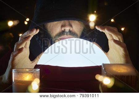 Very low key portrait of hooded man with eyes covered reading fortune on bright crystal ball, surrounded by candle light.