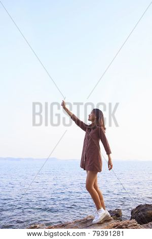 Portrait Of Young Beutiful Woman Rising Up Smart Phone To Sky Use For Feeling Of Human Communication