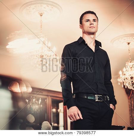 Handsome young well-dressed man in luxury house interior  poster